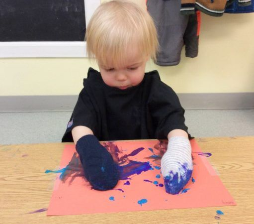 toddler_painting_with_socks_on_hands_next_generation_childrens_centers_beverly_ma-511x450