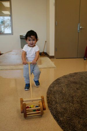 toddler_playing_with_lawn_mower_toy_smaller_scholars_montessori_academy_gilbert_az-300x450