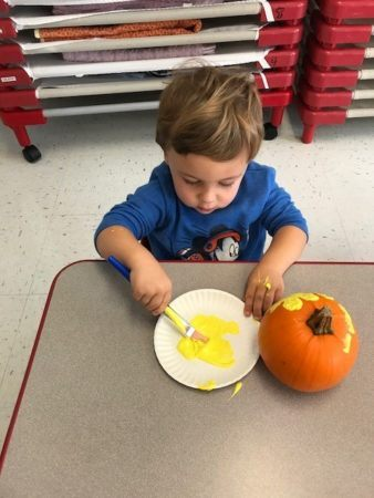preschooler_painting_pumpkin_yellow_winwood_childrens_center_south_riding_va-338x450